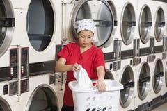 Panier de blanchisserie de transport des jeunes employés féminins avec des machines à laver à l'arrière-plan photo stock