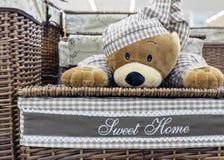 Panier de blanchisserie en osier avec un ours de nounours dans des pyjamas à carreaux photo libre de droits
