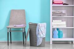Panier de blanchisserie en plastique avec des vêtements photos stock