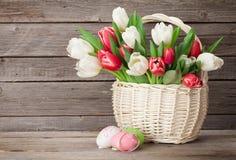 Panier de bouquet de tulipes et oeufs de pâques colorés Photo stock