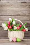 Panier de bouquet de tulipes et oeufs de pâques colorés Images stock