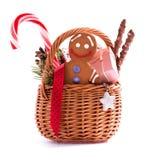 Panier de cadeau de Noël avec les festins et le bonhomme en pain d'épice d'isolement Photo stock