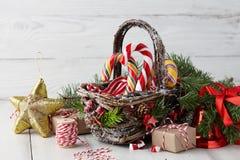Panier de Noël avec des cannes de sucrerie sur les planches blanches Photos stock