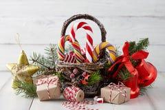 Panier de Noël avec des cannes de sucrerie sur les planches blanches Photo stock