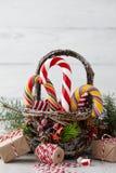 Panier de Noël avec des cannes de sucrerie sur les planches blanches Image libre de droits