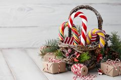 Panier de Noël avec des cannes de sucrerie sur les planches blanches Image stock
