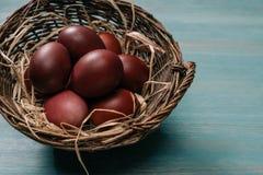 Panier de Pâques avec les oeufs et la paille peints Images libres de droits