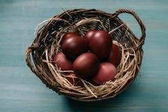 Panier de Pâques avec les oeufs et la paille peints Photo libre de droits