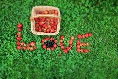 Panier de paille avec des fraises et le mot de ` d'AMOUR de ` de fraise Images stock