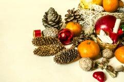 Panier de paille avec le fruit, les mandarines, le chocolat, les cônes et les écrous Photos stock