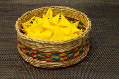 Panier de paille tissée avec le papier jaune photographie stock