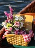 Panier de pique-nique avec des fleurs - sur un bateau en bois image libre de droits