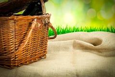 Panier de pique-nique et botle de vin sur la table avec le tissu de sac Photos stock