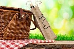 Panier de pique-nique sur la table et la bouteille de vin Photographie stock libre de droits