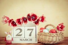Panier des oeufs et des fleurs de pâques sur la table en bois Photographie stock libre de droits