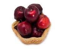 Panier des pommes rouge foncé sur un fond blanc Photo stock