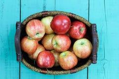 Panier des pommes rouges se reposant sur la table en bois Photographie stock