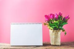Panier des roses roses décoratives avec le bloc-notes vide sur la vue supérieure f Photos stock