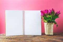 Panier des roses roses décoratives avec le bloc-notes vide sur la vue supérieure f Photographie stock libre de droits