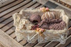 Panier du tricotage et des fils sur un banc Images stock
