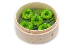 Panier en bambou de petits pains cuit à la vapeur par vert chinois d'isolement Photos libres de droits
