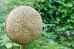 Panier en bambou en osier accrochant sur le bâton en bambou avec l'espace de copie Photo stock
