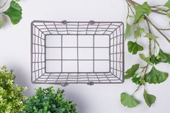 Panier en métal de fil avec la vue supérieure étendue par appartement de feuillage Image libre de droits