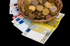 Panier en osier avec d'euro billets de banque et pièces de monnaie d'isolement Image stock