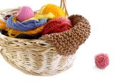 Panier en osier avec des boules des aiguilles de fil et de tricotage Image stock