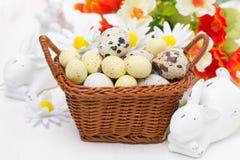 Panier en osier avec des oeufs de pâques et des lapins blancs Image stock