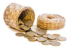 Panier en osier avec des pièces de monnaie Photo stock