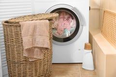Panier en osier avec la blanchisserie près de la machine à laver images stock
