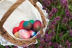 Panier en osier avec les oeufs de pâques colorés images stock