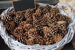 Panier en osier blanc complètement des cônes pour la décoration de Noël Photographie stock