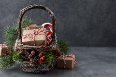 Panier en osier de Noël avec des cadeaux ou des boîtes actuelles Image libre de droits