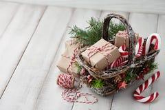 Panier en osier de Noël avec des cadeaux ou des boîtes actuelles Photos stock