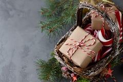 Panier en osier de Noël avec des cadeaux ou des boîtes actuelles Image stock