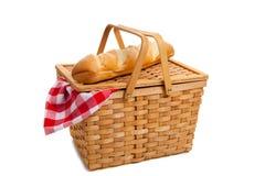 Panier en osier de pique-nique avec du pain sur le blanc Image libre de droits