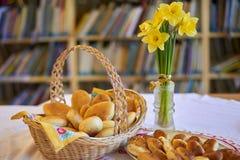 Panier en osier et plat rustiques complètement avec la série des pâtisseries, jonquilles jaunes dans le vase en verre, fond de bi photographie stock