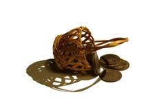 Panier en osier menteur avec les pièces de monnaie dispersées Image stock