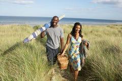Panier et coupe-vent de transport de pique-nique de jeunes couples Images stock
