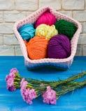 Panier et oeillets faits main tricotés sur les conseils minables bleus Photographie stock