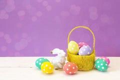 Panier jaune avec des oeufs de pâques et un lapin sur un backgrou pourpre Photographie stock