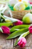 Panier, oeufs et tulipes de Pâques sur le panneau en bois Images libres de droits