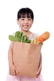 Panier que lleva de la pequeña muchacha china asiática con los ultramarinos Fotografía de archivo