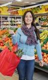 Panier que lleva sonriente de la mujer en tienda de la fruta foto de archivo