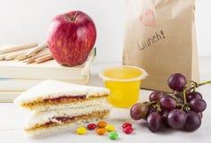 Panier-repas à l'école : sandwich avec le beurre d'arachide et la confiture, pomme, raisins, gelée sur un fond en bois blanc Photos stock