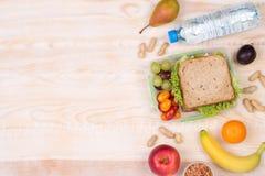 Panier-repas avec de l'eau le sandwich, les fruits, les légumes, et avec l'espace de copie photo libre de droits