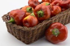 Panier rustique des poivrons de piment rouge sur le blanc Image stock