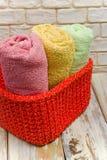 Panier tricoté fait main et serviettes sur les conseils portés blancs photo stock